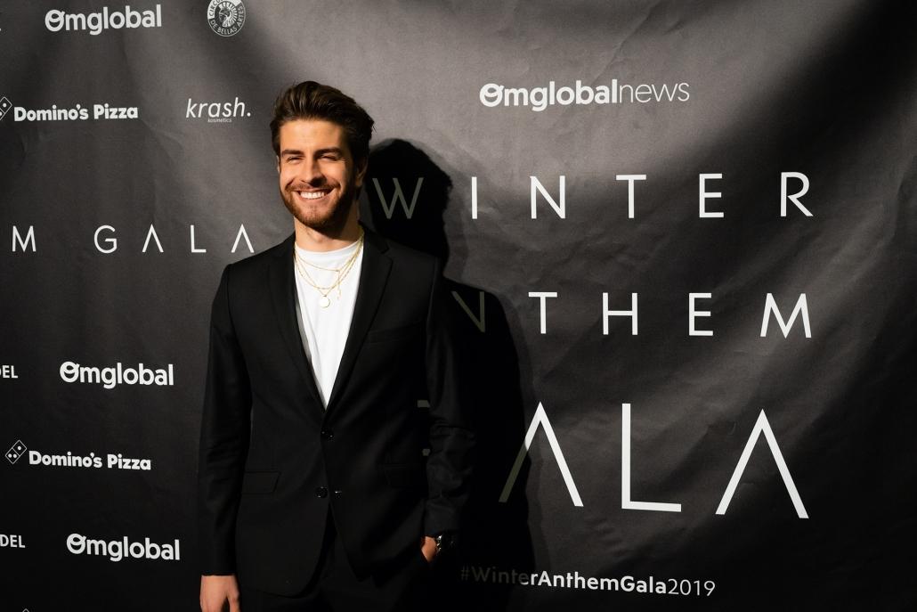 El actor y creador de 9TheBrand Mario Marzo (@mario_marzo) vestido con traje negro, camiseta blanca y joyería de @9thebrand